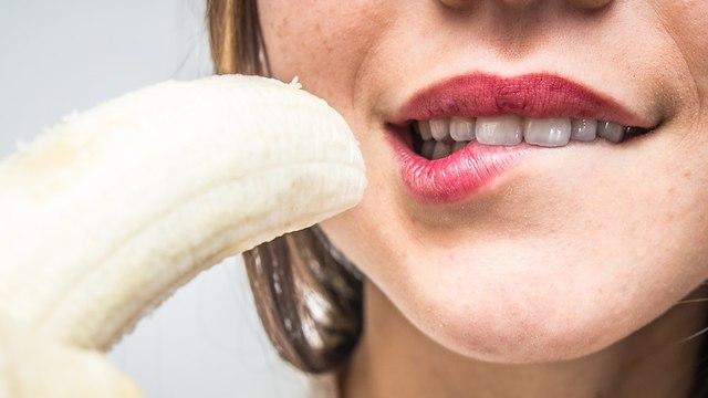 אילוסטרציה של אישה אוכלת בננה (צילום: Shutterstock)
