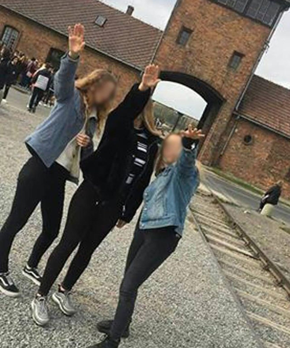 Polish teenage girls doing a Nazi salute during a visit to Auschwitz.