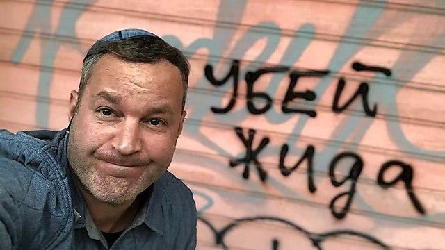 David Roitman next to spray-painted writing calling to 'kill Jews'    (Photo: David Roitman)
