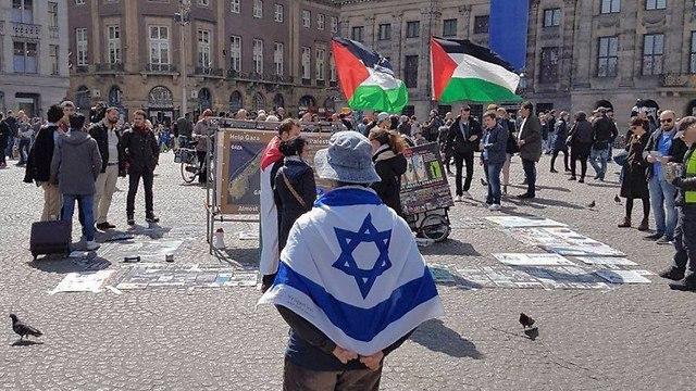 יהודי באמסטרדם שמפגין לבדו עם דגל ישראל ענק מול הפגנות הסתה של ה- BDS ()