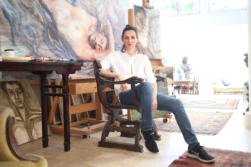 """""""כשאנחנו במקומות הכי שבורים, אנחנו הכי יפים"""". יעל רייך בביתה, מוקפת בעבודת אמנות שלה (צילום: תומריקו)"""
