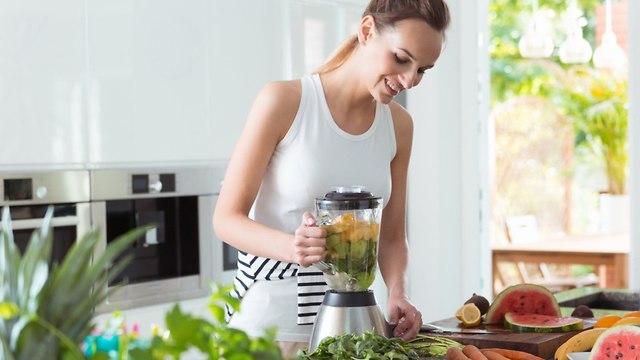 אישה מכינה שייק במטבח (צילום: shutterstock)
