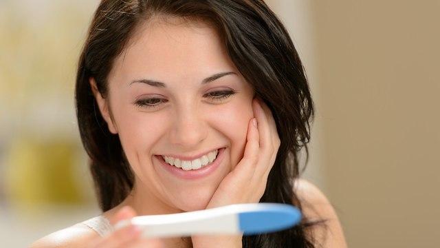 אישה מחייכת עם בדיקת היריון (צילום: shutterstock)