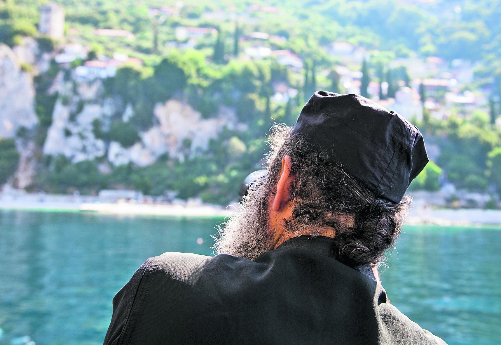 נזיר צופה מהמעבורת לעבר מנזר אנה הקדושה. שקי סחורה, משאיות עמוסות ועשרות עולי רגל