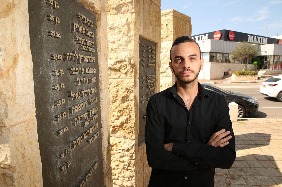ג'ורג' מטר ליד מסעדת מקסים בחיפה והאנדרטה שעליה מופיעים שמותיהם של 21 ההרוגים, ובהם בן דודו של אביו - ג'ורג' מטר (צילום: אלעד גרשגורן)