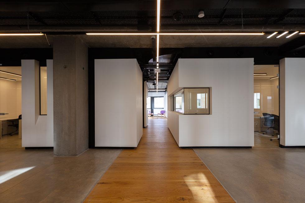 למרות היותה של הקובייה האוביקט הכי אטום במרחב, היא נראית קלילה ואוורירית הודות לחריצה העמוקה של החלונות ודלתות הזכוכית, ששוקעו בעומק הקיר. צוקל שחור מקיף אותה ומנתק אותה חזותית מהרצפה ומהתקרה. שביל עץ חוצה אותה לשתיים וממשיך לעבר החצר הפנימית (צילום: Miri Nagler)
