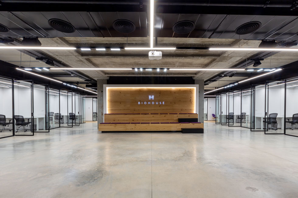 מרחב התכנסות בקומה התחתונה מזכיר אמפיתאטרון. משני צדיו משרדים שקופים, ומאחוריו קובייה לבנה למשרדים סגורים ופרטיים יותר (צילום: Miri Nagler)