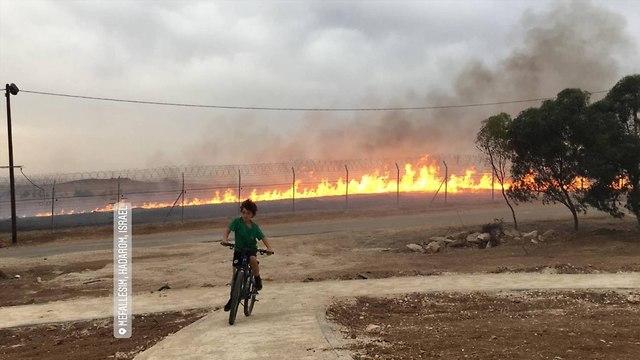 Yonatan Regev pedaling away from the fire (Photo: Uriya Kabir)