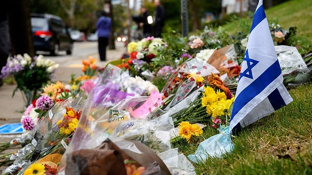 מניחים פרחים מחוץ לבית הכנסת עץ החיים בפיטסבורג פנסילבניה (צילום: AFP)