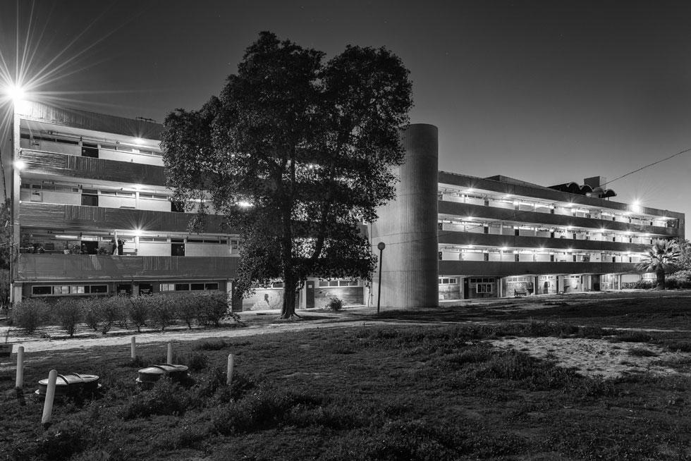 מעון העולים ''אלטשול'', שמתנוסס על כריכת הספר ''אדריכלות קונקרטית'' מאת שרון רוטברד על האדריכל אברהם יסקי, הושחת בתוספות מכוערות. כאן, בצילום הלילי, הצליח הצלם אלי סינגלובסקי ללכוד את ייחודו של המבנה (צילום: אלי סינגלובסקי, אלטשול1, 2015, צילום שחור לבן)