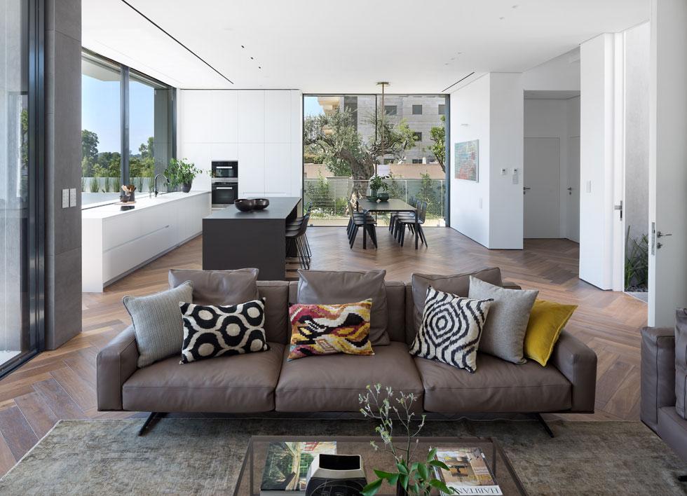 שטחו של הבית 360 מ''ר, המתפרשים על פני שתי קומות ומרתף. הסלון והמטבח פתוחים אל הסביבה, בחלונות רחבים עם משקופים נסתרים (צילום: שי אפשטיין)