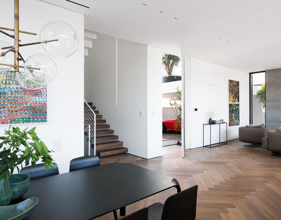 דלת הכניסה הלבנה נפתחת אל הסלון. על הקיר בפינת האוכל תלויה עבודה של יוסי בכר, שנבחרה בעזרתה של אוצרת שעובדת עם האדריכלים (צילום: שי אפשטיין)