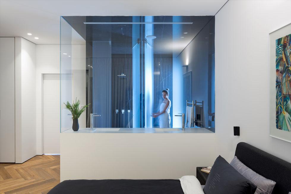 בחדר ההורים מפריד קיר זכוכית את אזור השינה מאזור הרחצה. בחלקו התחתון שידת כיור לבנה, שמראה עולה ממנה בלחיצת כפתור (צילום: שי אפשטיין)