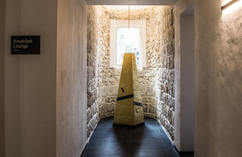 במבנה הישן שומרו הבליטות המקומרות בחזית, מעין קפלות, שבהן הושארה אבן הגיר המקורית חשופה. גיל גורן, האחראי על האמנות במלון, יצר גם את הפירמידה המוזהבת (צילום: איתי סיקולסקי)