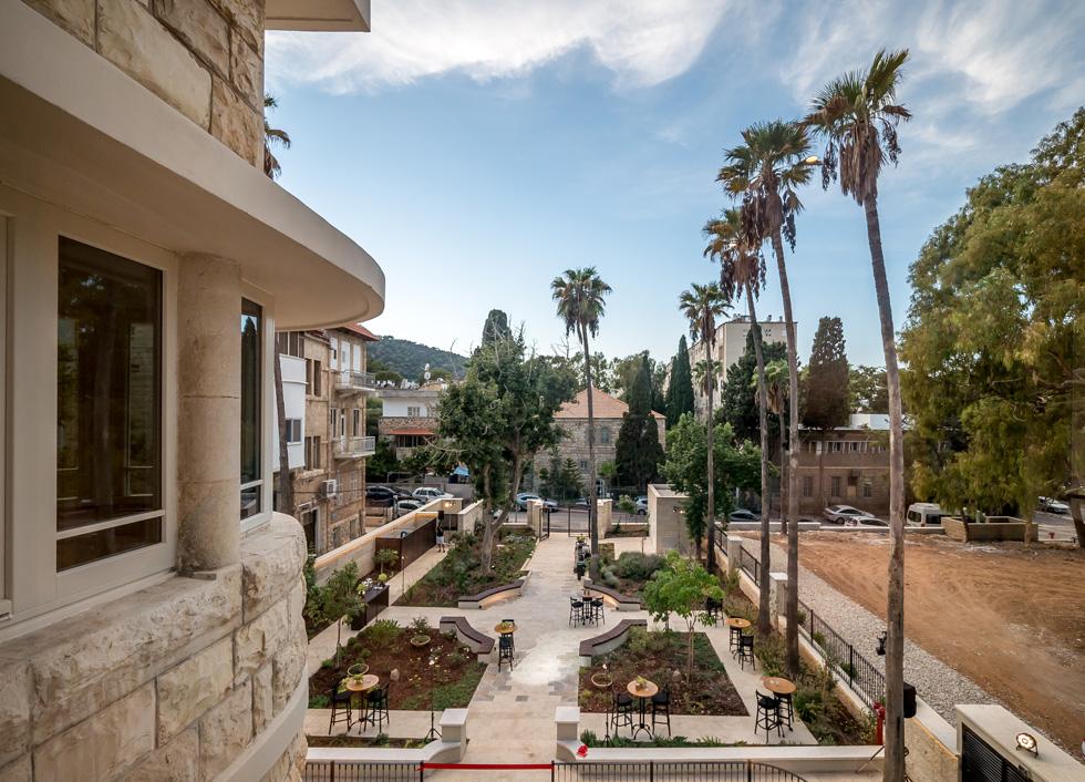 בקדמת המבנה ההיסטורי חצר אבן גדולה ומטופחת, עם ערוגות של צמחייה ארץ-ישראלית בגיאומטריה סימטרית (צילום: איתי סיקולסקי)