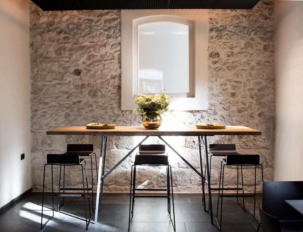 קיר אבן מקורי בחדר ארוחת הבוקר. דרישות השימור התייחסו רק למעטפת המבנה, ועיצוב הפנים השאיר רק מעט מהישן. כך, למשל, הוחלפו המרצפות המאוירות באריחי גרניט-פורצלן שחורים (צילום: איתי סיקולסקי)