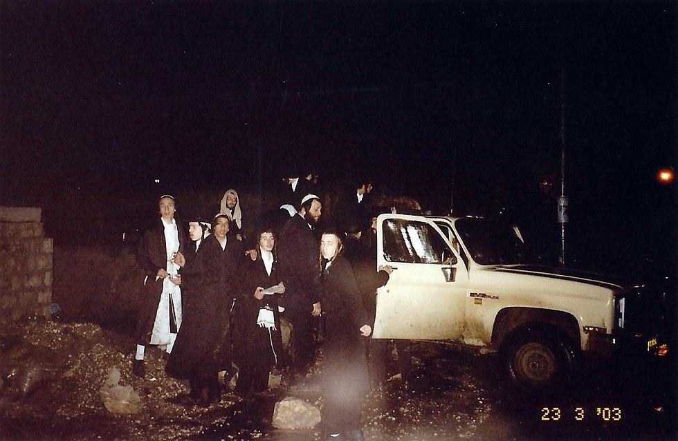 יורדים מהמשאית לתפילה בקבר, בהסתננות. פברואר 2003 (צילום: נחמן וייס ושלמה טובול)