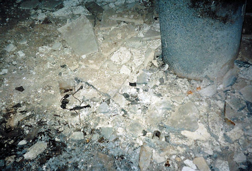 שרידי המטען שהתפוצץ בתוך הקבר, סמוך למצבות, בקיץ 2002 (צילום: נחמן וייס ושלמה טובול)