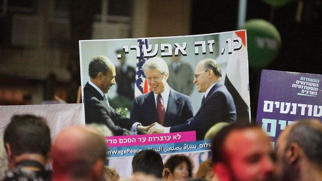 Banner at the Rabin memorial rally saying 'Yes, it's possible' with a picture of Israeli Prime Minister Menachem Begin and Egyptian President Anwar Sadat shaking hands at the Israel-Egypt peace treaty signing, with US President Bill Clinton looking on.  (Photo: Motti Kimchi)