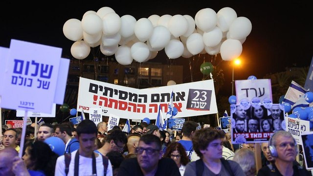Banners at the Rabin memorial rally saying 'Peace belongs to everyone' (left) and '23 years, the same inciters, the same incitement!' (center) (Photo: Motti Kimchi)