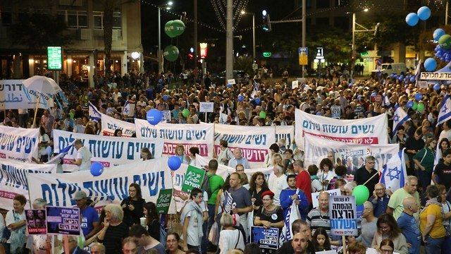 The audience at the Rabin memorial rally holding up signs calling for peace (Photo: Motti Kimchi)