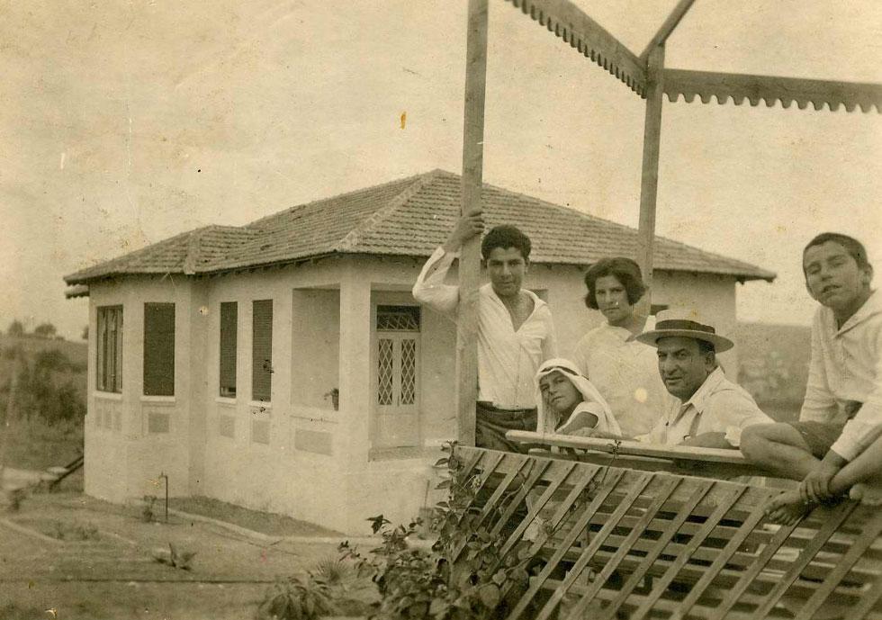 משפחת קריניצי על רקע הבית, בתצלום מ-1927. שנה קודם לכן התמנה האב לכהן כראש העיר הצעירה, ולא מש מכיסאו (צילום: ארכיון בית קריניצי, בית העיר רמת-גן)
