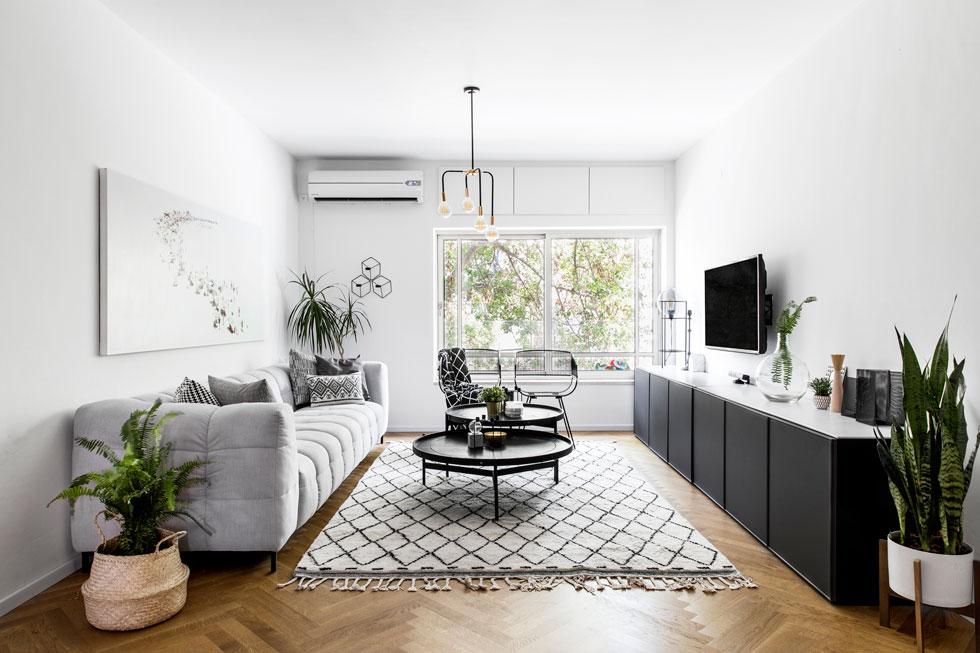 """בסלון מזנון איקאה שהורכב משתי יחידות ומולו ספה אפורה. על הקיר עבודה של רוני בן-שמחון. """"שהייתה חייבת להישאר"""", אומרת האם, """"בעלי אמר לשרית: 'לא אכפת לי מה תעשי פה, אבל התמונה נשארת'"""". על הרצפה שטיח בדוגמה גיאומטרית, כמו ביתר חדרי הבית (צילום: איתי בנית)"""