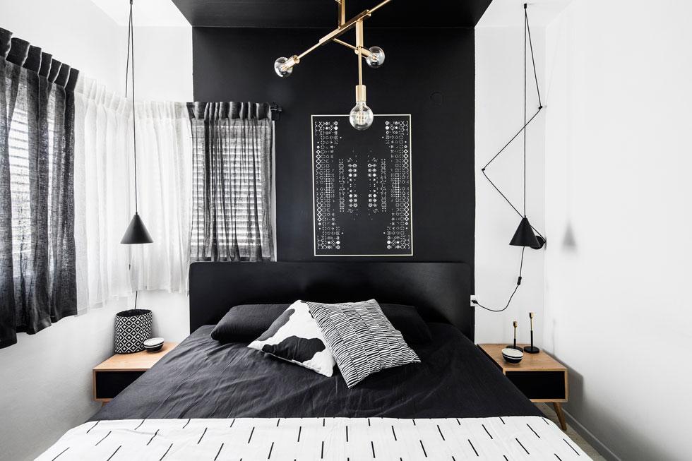 במרכז חדר ההורים מיטה שחורה, ומנורות קריאה שחורות יורדות מעל שידות צד מעץ. האלמנט המרכזי הוא הפס השחור הרחב שמטפס על הקיר בגב המיטה, אל התקרה. גם הווילונות הותאמו לפס הצבוע (צילום: איתי בנית)