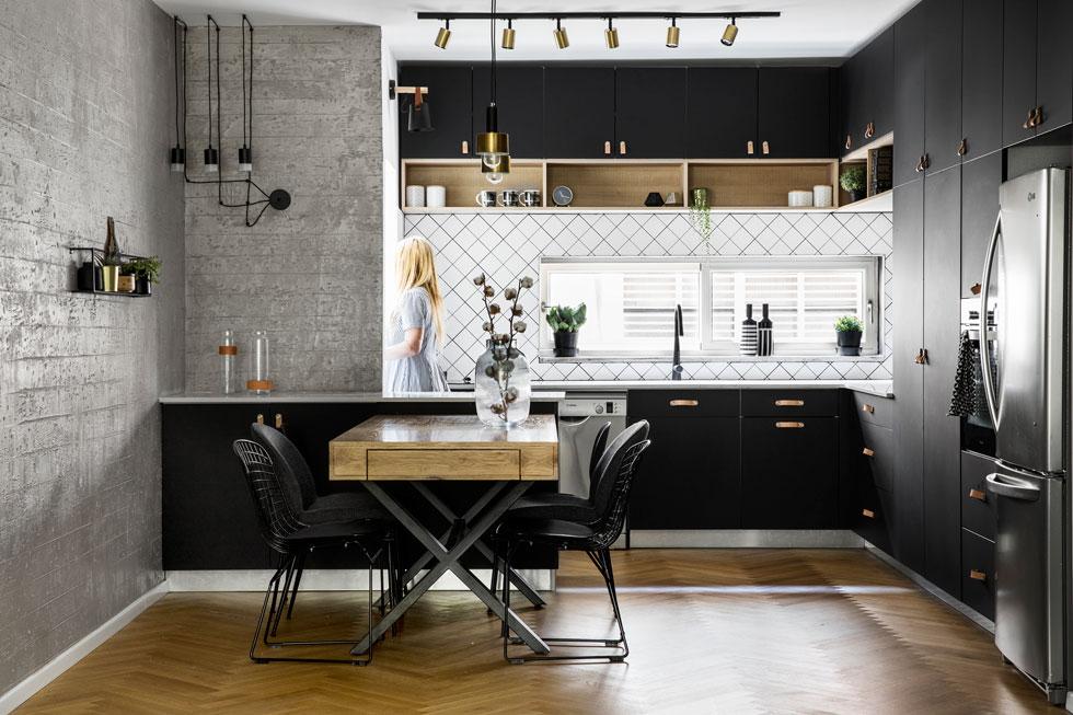 """במטבח, בסלון ובפרוזדור כוסתה הרצפה בפרקט אלון.  """"בגלל שהצבעים קרים היה חשוב לי שתהיה תחושה חמימה"""", אומרת המעצבת שרית זיו-אלון. """"לכן הוספתי את הבטון, את ידיות העור לארונות המטבח ואת העץ"""" (צילום: איתי בנית)"""