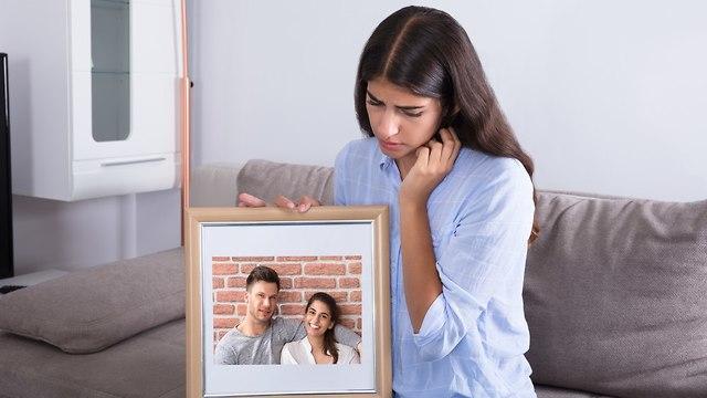 אישה מביטה על תמונת אהובה בעצב (צילום: Shutterstock)