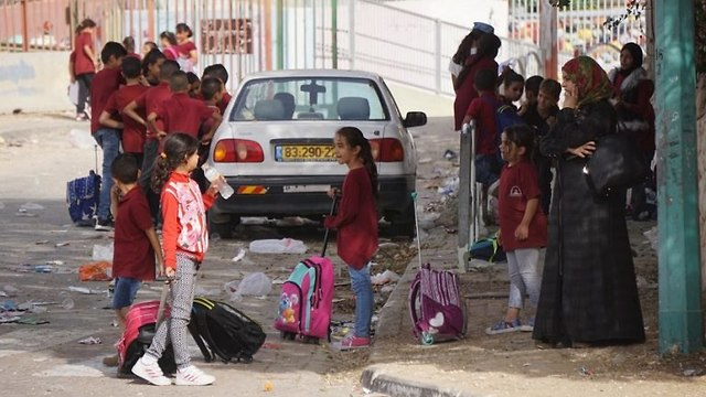 A woman and schoolchildren stand near a street in Rahat (Photo: Victor Cabrera)