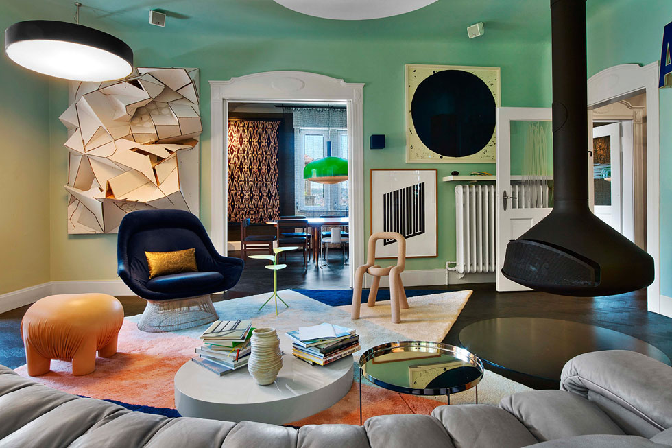 צורניות הסלון אמורפית. פריטים מעוגלים - כמו הספה, הקמין המרחף והעיגולים שצוירו על התקרה - מנוגדים לזוויות הגרפיות בשטיח ובעבודת הקיר הגדולה. חדר האוכל מציץ דרך הפתח הבא (צילום: Eric Laignel)