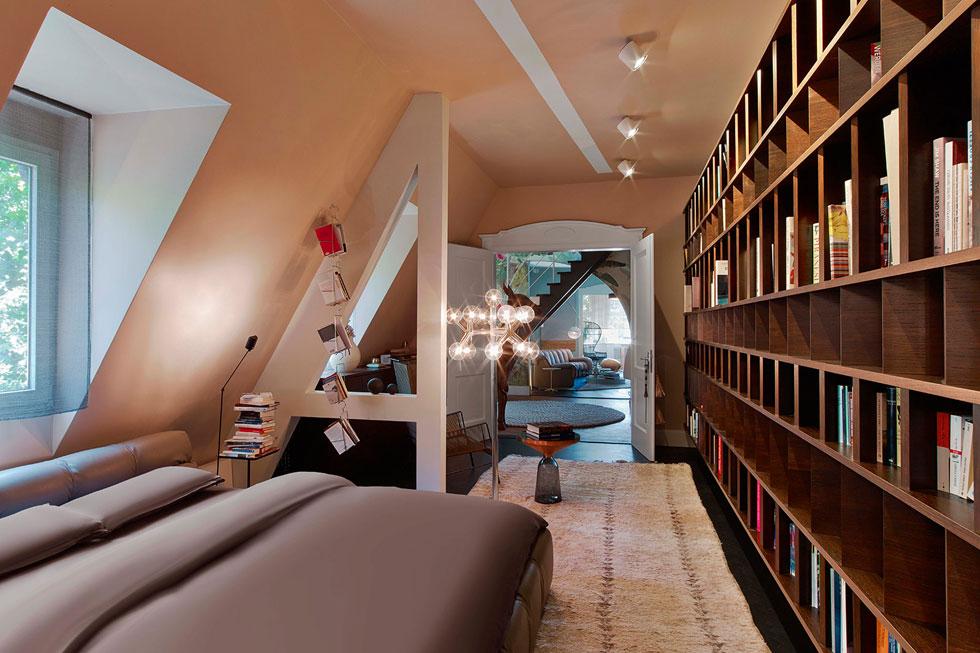 דלת דו-כנפית מובילה אל חדר השינה, שבו ספרייה המלווה את ההולכים עד לאמבטיה. העץ הכהה, יחד עם גוון הקירות האלגנטי ושטיח המשי, משווים עדינות ושקט (צילום: Eric Laignel)