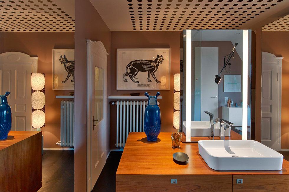 חדר הרחצה מרווח. קירותיו נצבעו בגוון סלמון, ובמרכז מוקמה יחידת כיור חופשית (''פרי סטנדינג''). מראות יוצרות אשליית הגודל, ומאפשרות קשר עין עם שאר החדרים (צילום: Eric Laignel)