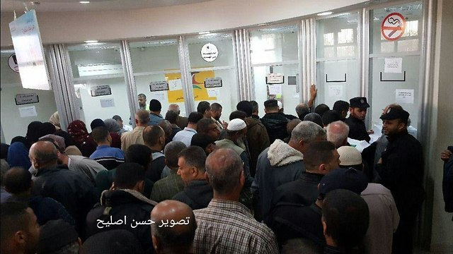 Hamas officials arrive at the post office to receive salaries paid by Qatar
