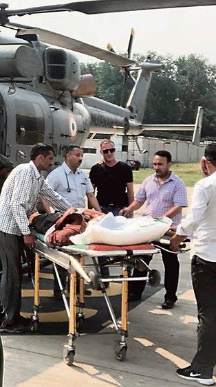 Consul Eli Sneh, in black, helps evacuate Israeli injured in India