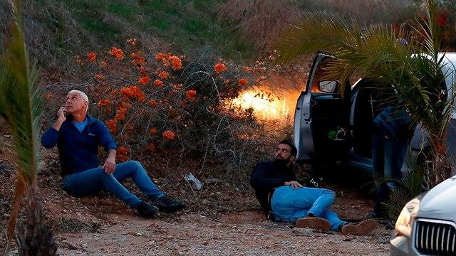 אנשים תופסים מחסה בשדרות ירי רקטות מ עזה (צילום: AFP)
