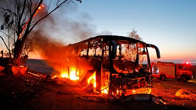 An IDF bus burning after it was hit by an anti-tank missile near the Gaza border in November 2018  (Photo: AFP)