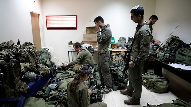 Troops prepare their combat gear (Photo: Reuters)