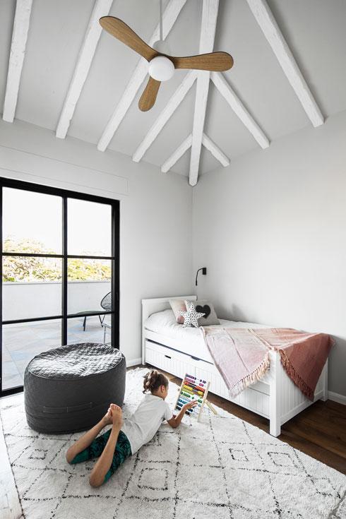 על התקרה המשופעת בחדרי הילדים קורות עץ לבנות (צילום: איתי בנית)