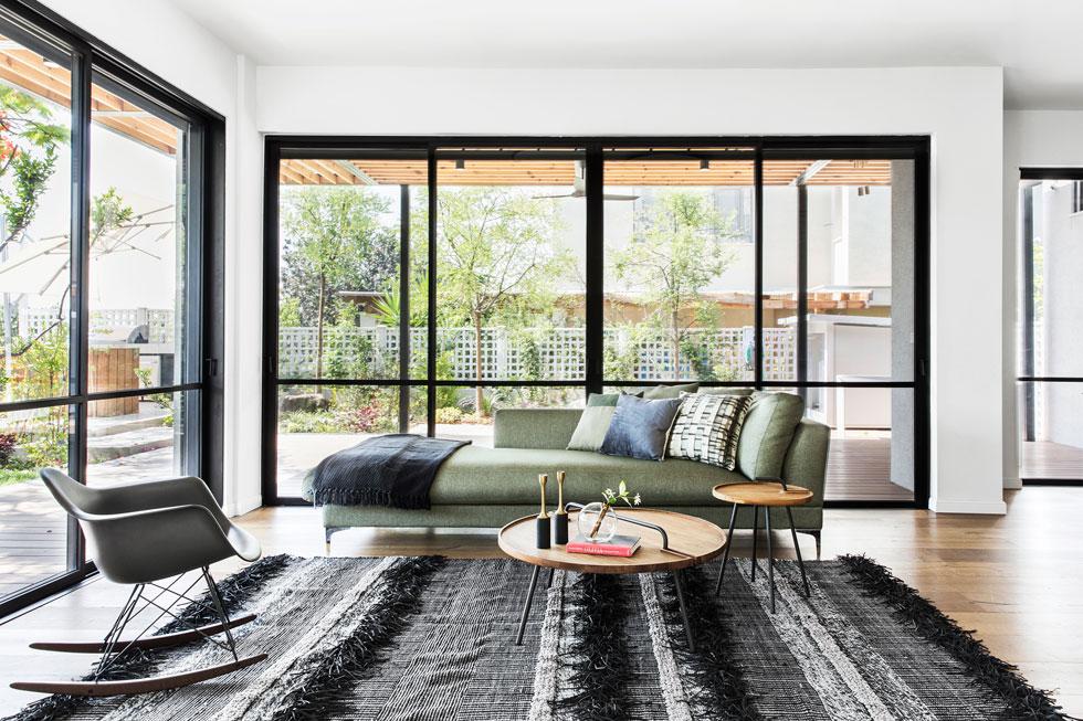 הסלון מרוהט באווריריות, ומוקף קירות זכוכית הפונים לגינה וליער. בני הזוג, הורים לשלושה בנים, גרים בשוהם שנים, וחיפשו בית מרווח יותר (צילום: איתי בנית)