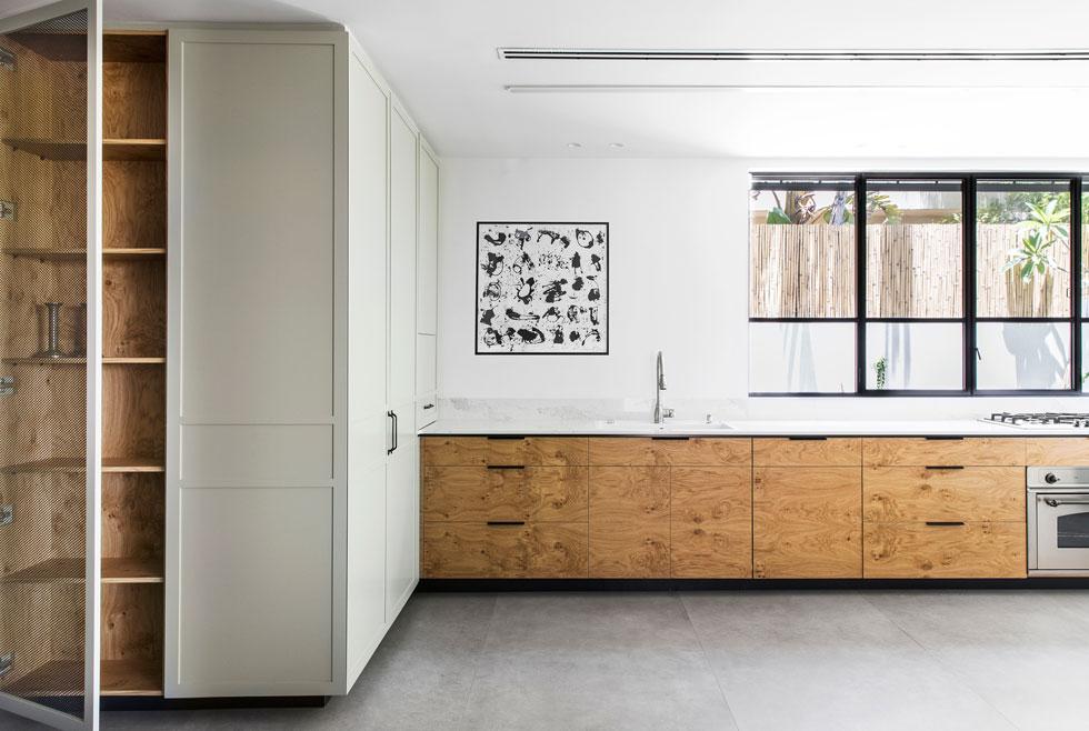 המטבח תוכנן כציר ארוך בצד הבית. הדלתות של הארונות עשויות משורש אלון צרפתי, שמוסיף למכלול העדין חומריות טבעית ומחוספסת יותר (צילום: איתי בנית)