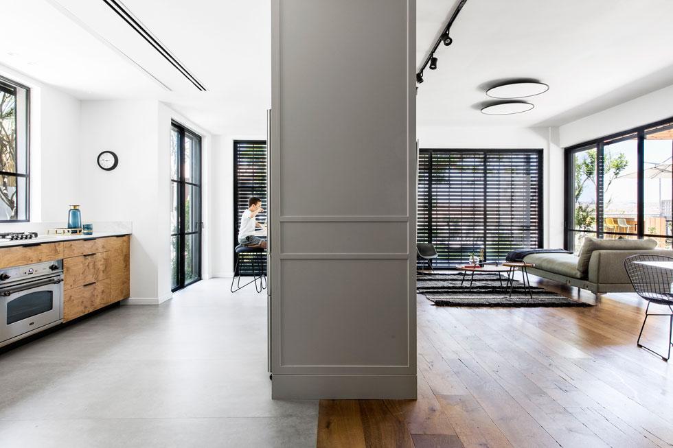 מבט מאחד המעברים הרחבים אל יחידת הנגרות שעוטפת מצד המטבח את המקרר, ומצד הסלון משמשת כקיר טלוויזיה (צילום: איתי בנית)