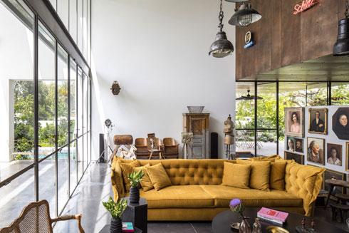 לצד הסלון קיר נמוך עם תמונות פורטרט, בגבו קיר לבן ובעברו השני קיר זכוכית (צילום: עמית גרון)