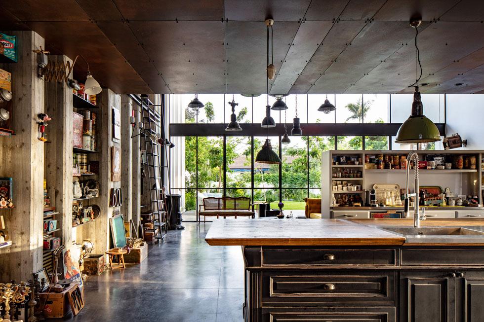 קיר זכוכית עצום פונה לגינה האחורית. על עיצוב המטבח, כמו פרטי נגרות אחרים, אחראית בעלת הבית במשותף עם נגריית שורש. הם שילבו אלמנטים בעלי גוון רומנטי (צילום: עמית גרון)