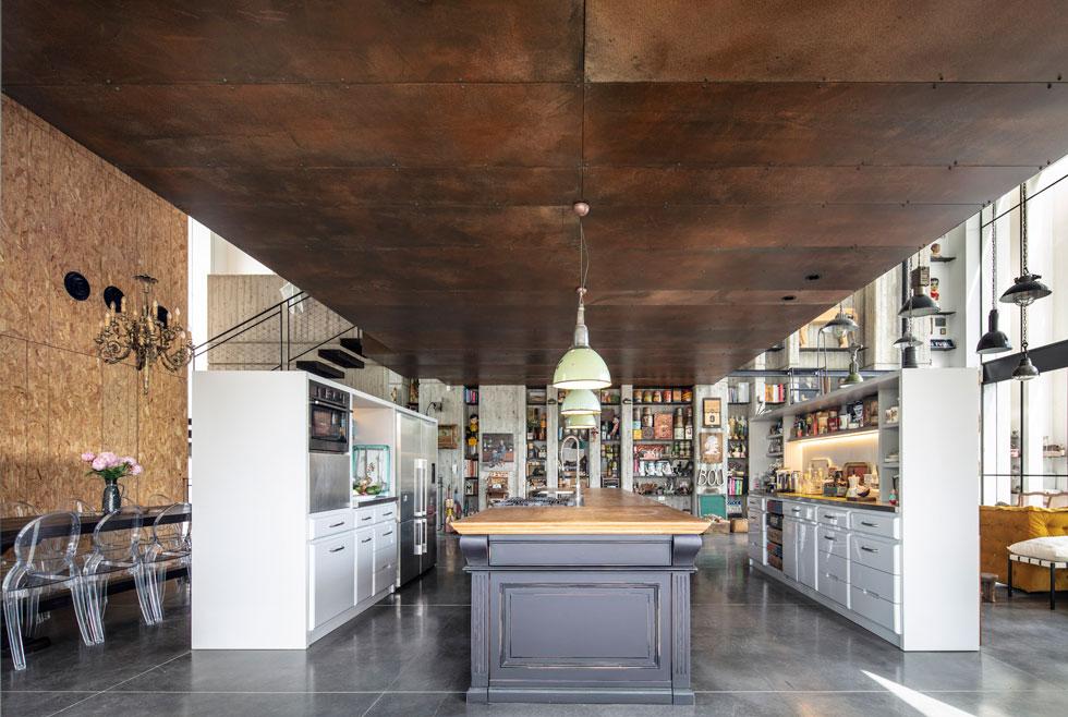 המטבח ממוקם במרכז קומת הכניסה, תחת תיבת הפלדה, המהווה לו תקרה מונמכת. הוא מורכב משלושה מקבילים: שני פסים של ארונות ואי גדול. פינת האוכל משמאל, תחומה בקיר שכוסה בלוחות OSB (שבבי עץ דחוסים) (צילום: עמית גרון)