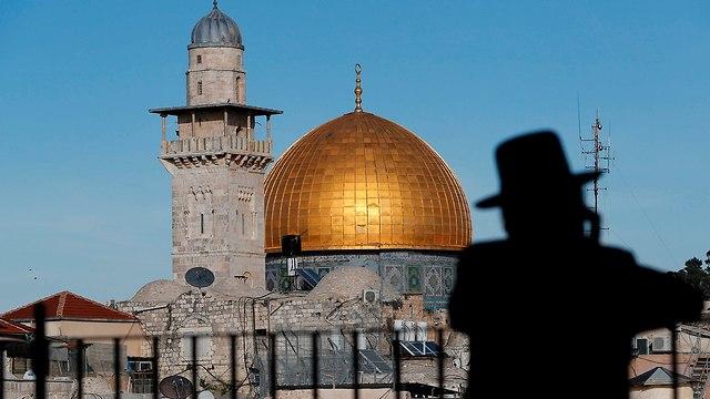 חרדי בירושלים על רקע הר הבית (צילום: AFP)
