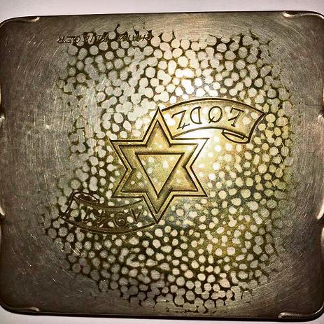 The engraved silver cigarette case.