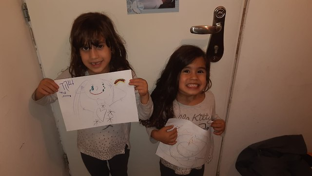 Gaya and Shaked from Sderot hold up their drawings