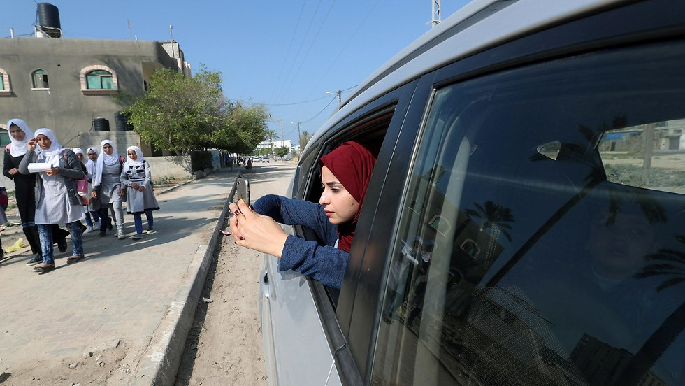 Fatma Abu Musabbeh uses her mobile phone to take pictures as she looks out of a car window in the central Gaza Strip (Photo: Reuters)